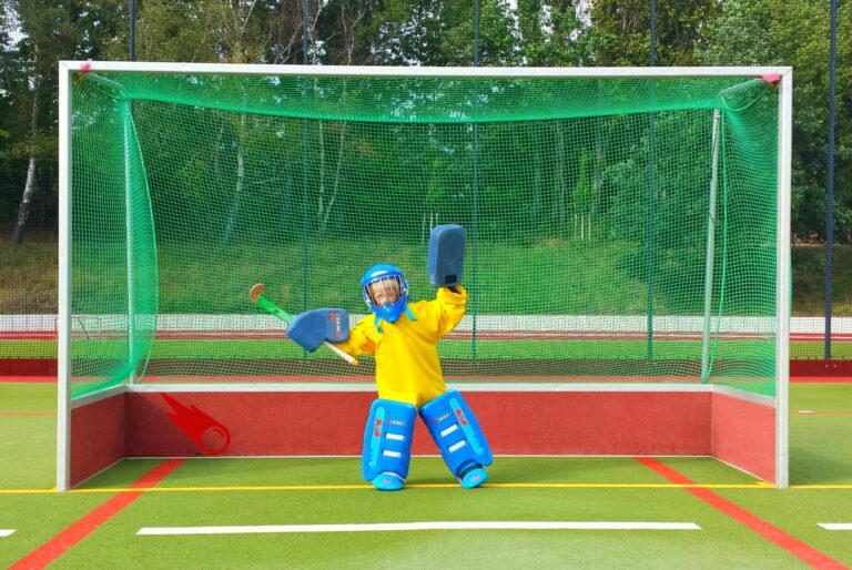 junger Torwart steht in Rüstung im Hockeytor