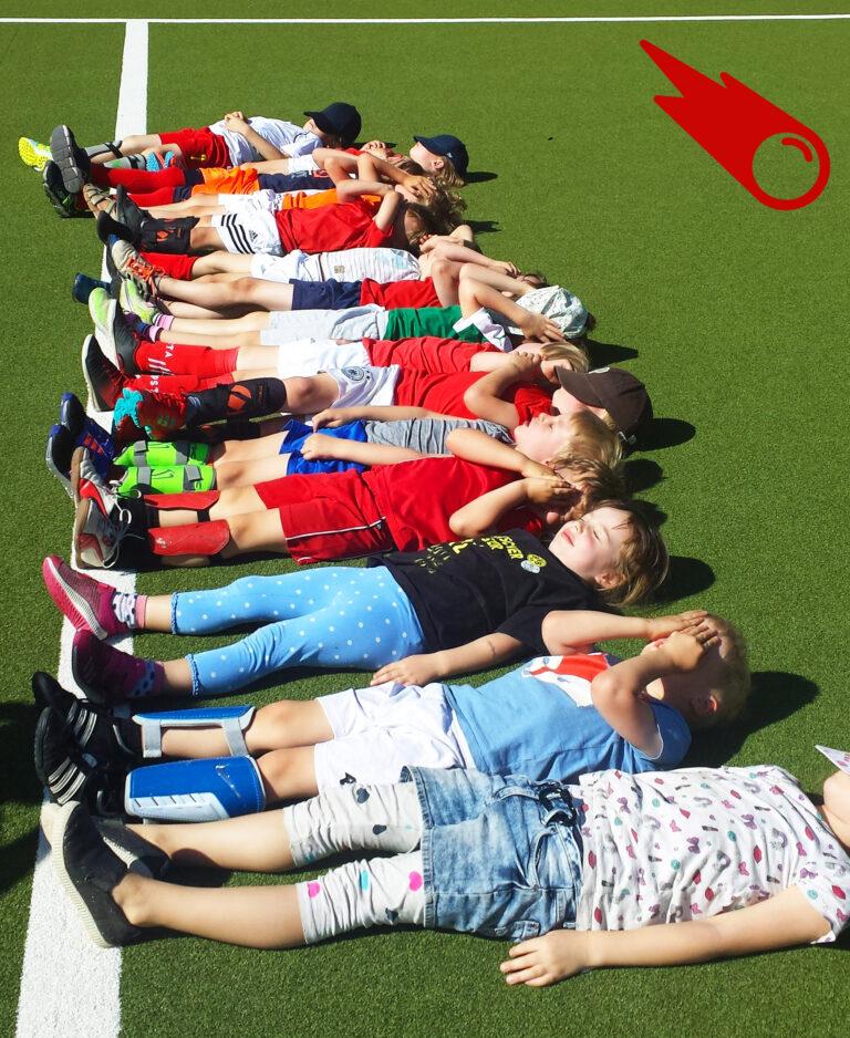 einige Kinder liegen auf dem Rücken nebeneinander mit geschlossenen Augen auf dem Kunstrasenplatz