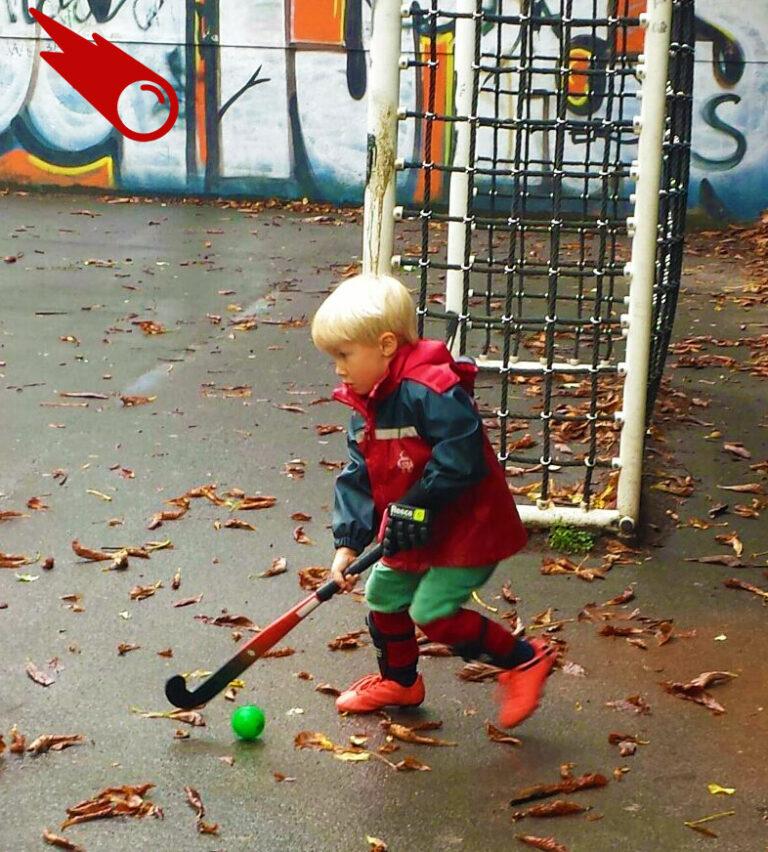 kleiner Junge spielt Hockey auf Bolzplatz